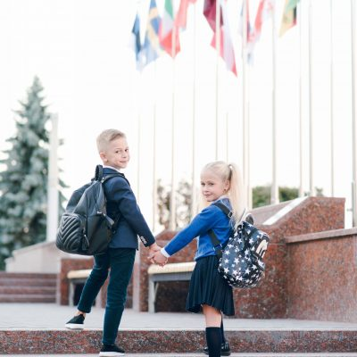 Little students go to school. Schoolchildren on background of fl