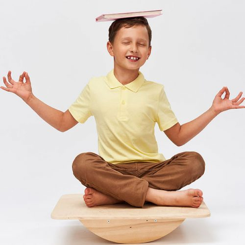 small boy holds book on his head while balancing on special simulator for training muscles. child is engaged on balance beam, an intermediate internal balance. Training development cerebellum.